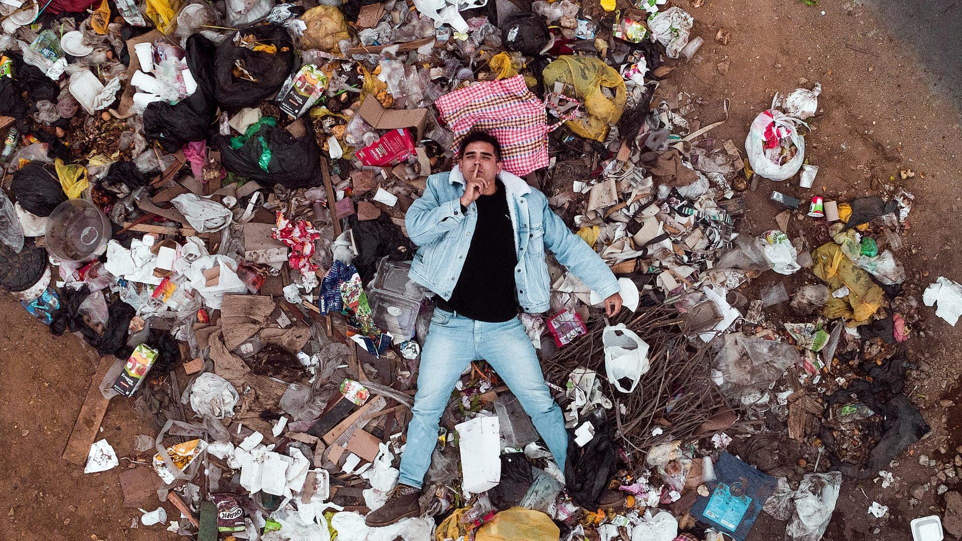Mand ligger i en bunke affald på stranden · Sonforce · Sønderborg Forsyning